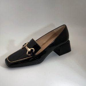 Mocasín en charol negro con detalle de cadena oro y estribo dorado. Suela de goma y tacón ancho de 4,5 cm.